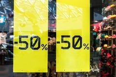 在布料商店的销售标志 贴纸-由半价格决定与衣裳的50%窗口在冬天季节期间 免版税库存图片