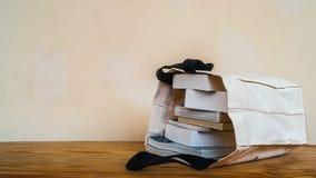 在布料袋子里面的书在木桌上 免版税库存照片