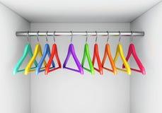 在布料路轨的五颜六色的挂衣架在衣橱 免版税库存图片
