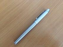 在布朗书桌上的银色笔 免版税图库摄影