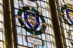 在布赖顿徽章的两只海豚在五颜六色的污迹玻璃窗的在奇切斯特大教堂-大教堂教会里圣洁 免版税库存照片