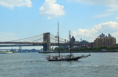在布鲁克林大桥旁边的飞剪机城市高船 库存图片