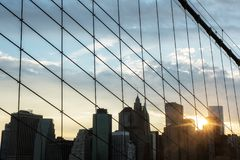 在布鲁克林大桥的华尔街大厦在日落时间 库存照片