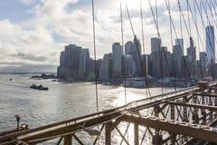在布鲁克林大桥的钢结构后您能看到曼哈顿摩天大楼和距离的Lber雕象  图库摄影