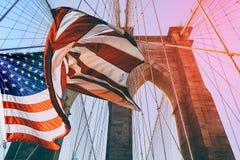 在布鲁克林大桥顶部的美国旗子 有在背景的深蓝天,在那里前景是所有导线  库存图片