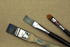 在帆布的三支画笔 免版税库存照片