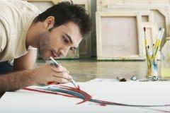 在帆布的人绘画在演播室地板上 免版税库存照片