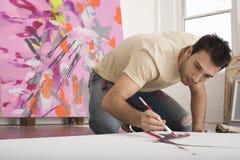在帆布的人绘画在演播室 图库摄影