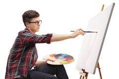 在帆布的十几岁的男孩绘画 免版税库存照片