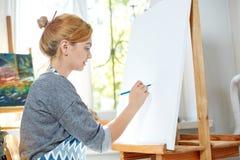 在帆布的年轻微笑的女孩油漆与油漆在自己的车间 在背景的窗口 艺术背景黑色概念屏蔽油漆红色地点白色 免版税库存照片