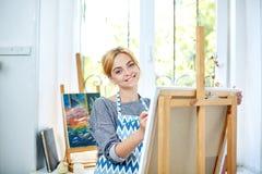 在帆布的年轻微笑的女孩油漆与油漆在自己的车间 在背景的窗口 艺术背景黑色概念屏蔽油漆红色地点白色 库存图片