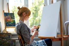 在帆布的年轻微笑的女孩油漆与油漆在自己的车间 在背景的窗口 艺术背景黑色概念屏蔽油漆红色地点白色 免版税图库摄影