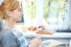 在帆布的年轻微笑的女孩油漆与油漆在自己的车间 在背景的窗口 艺术背景黑色概念屏蔽油漆红色地点白色 图库摄影