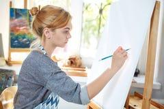 在帆布的年轻微笑的女孩油漆与油漆在自己的车间 在背景的窗口 艺术背景黑色概念屏蔽油漆红色地点白色 库存照片