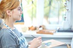 在帆布的年轻微笑的女孩油漆与油漆在自己的车间 在背景的窗口 艺术背景黑色概念屏蔽油漆红色地点白色 免版税库存图片