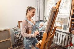 在帆布的微笑的女孩油漆与油漆在车间 免版税库存图片