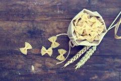 在帆布的未煮过的意大利面团farfalle一点袋子 免版税库存照片