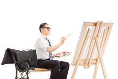 在帆布的男性商人绘画 库存图片