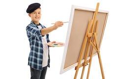 在帆布的逗人喜爱的小男孩绘画 免版税库存照片