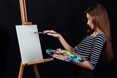 绘在帆布的逗人喜爱的美丽的女孩艺术家一幅画画架 文本的空间 演播室黑背景 免版税图库摄影