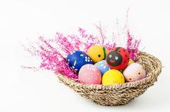 在帆布篮的复活节彩蛋与桃红色花 免版税库存图片