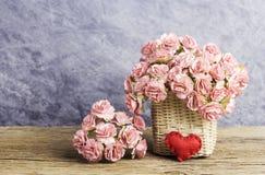 在帆布篮的桃红色纸康乃馨与在老木头的红色心脏 图库摄影