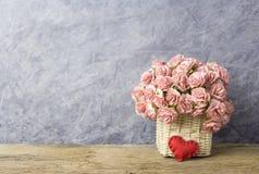 在帆布篮的桃红色纸康乃馨在老木头 库存图片