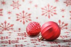 在帆布背景的红色圣诞节装饰品与红色闪烁雪花 免版税图库摄影