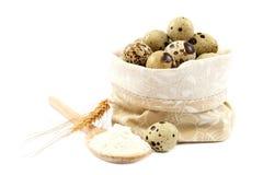 在帆布袋子的在一把木匙子的鹌鹑蛋和面粉 库存照片