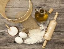 在帆布袋子的小麦面粉,筛子,在玻璃玻璃水瓶,大盐瓶木头,未加工的鸡蛋,一根木滚针的橄榄油:集合 图库摄影