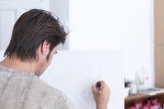 在帆布-绘画会议的年轻画家图画 库存照片