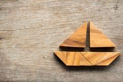 在帆船形状的七巧板难题在木背景 库存照片