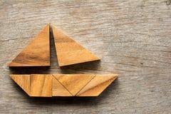 在帆船形状的七巧板难题在木背景 免版税库存照片