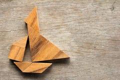 在帆船形状的中国七巧板难题在木背景 免版税图库摄影