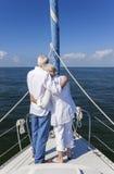 在帆船的前面的愉快的高级夫妇 库存照片