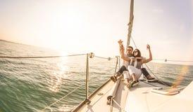 在帆船的年轻恋人夫妇用在日落-与富有的千福年的人生活方式的专属豪华概念的香槟在游览中 免版税图库摄影