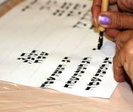 在希伯来语的书法文字 递笔 词组Chag Chanukah Sameach翻译了愉快的光明节 抄写员sofer 免版税库存照片