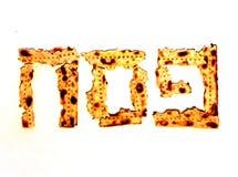 在希伯来语的题字由未发酵的面包Pesach片断  犹太逾越节 残破的未发酵的面包 白色查出的背景 库存照片