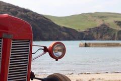 在希望小海湾海滩,德文郡,英国的老红色拖拉机前面 库存图片