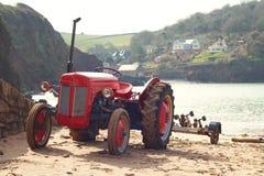 在希望小海湾海滩,德文郡,英国的老红色拖拉机 免版税图库摄影