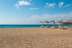 在希腊使俯视绿松石水的sunbeds和遮阳伞靠岸 库存照片