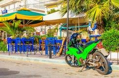 在希腊餐馆前面的绿色摩托车 免版税图库摄影