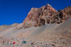 在帐篷旁边的人在山 库存图片
