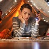 在帐篷的一间屋子里读与一个灯笼的美女一本书,有灯的 睡眠、读书、文学和梦想的概念 库存照片