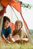 在帐篷的男孩和女孩读书 免版税库存图片