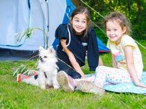在帐篷的阵营-有一起坐在帐篷附近的小犬座奇瓦瓦狗的女孩 图库摄影