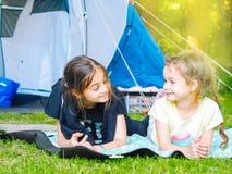 在帐篷的阵营-有一起坐在帐篷附近的小犬座奇瓦瓦狗的女孩 库存图片
