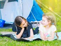 在帐篷的阵营-有一起坐在帐篷附近的小犬座奇瓦瓦狗的女孩 免版税库存图片