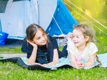 在帐篷的阵营-有一起坐在帐篷附近的小犬座奇瓦瓦狗的女孩 库存照片