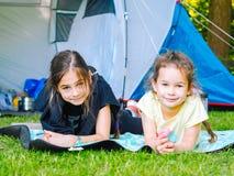 在帐篷的阵营-有一起坐在帐篷附近的小犬座奇瓦瓦狗的女孩 免版税图库摄影